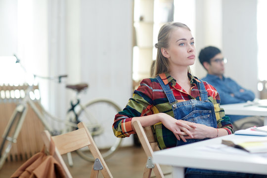 Absent minded girl sitting by desk at lesson