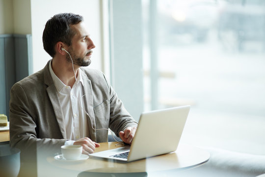 Portrait of mature pensive man looking away to window while using laptop in cafe, with earphones