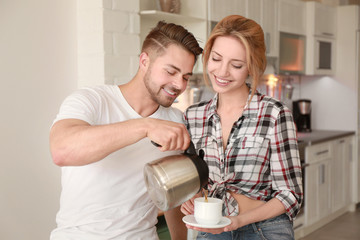 Morning of happy young couple drinking tea in kitchen
