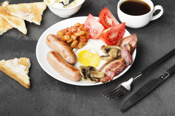 Foto op Aluminium Sushi bar Traditional English breakfast - bacon, sausages, fried eggs, tomatoes, beans, mushrooms, toast with butter - in white plate and coffee on a dark background