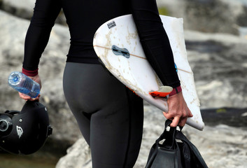 A surfer's broken board is retrieved from the ocean during the Cape Fear surfing tournament in heavy seas off Sydney's Cape Solander in Australia