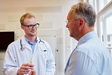 Hausarzt und Patient mit Urinprobe