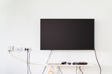 lcd tv on wall with remote, wireless internet access point and set top box