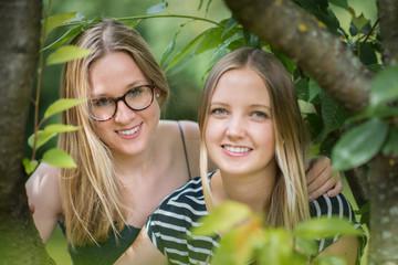 Zwei blonde Mädchen im Portrait - 2 Frauengesichter zwischen den Bäumen