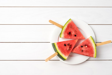 Overhead shot of watermelon slices on white wooden background