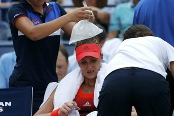 A ball girl places a bag filled with ice on the head of Mladenovic of France as she tries to cool off between games during her quarterfinals match against Vinci of Italy at the U.S. Open Championships tennis tournament in New York