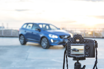 A Photo camera taking pictures of modern car on the roof of building at the sunset