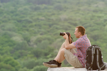 Man takes pictures from a hill in the background of forest