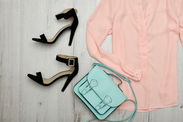Peach blouse, black shoes, handbag. Fashionable concept. Wooden background