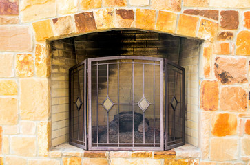 Limestone outdoor fireplace with mesh grate