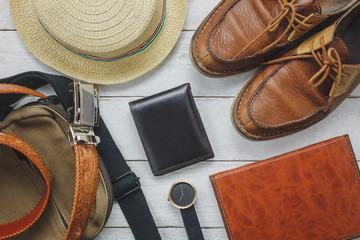 Top view accessories to travel with man clothing concept. wallet on wooden background.watch,bag,hat,notebook and shoe on white wood table.