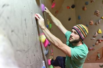 bouldern in einer Kletterhalle - junger Mann klettert eine künstliche Felswand empor // Bouldering in a climbing hall
