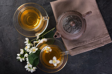 Glass cups of tea and tea pot with jasmine on  a dark  background.