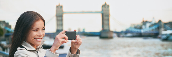 London woman tourist taking photo of Tower Bridge banner panorama. London woman taking photos with mobile smart phone camera. Girl at River Thames, London, England, Great Britain. UK tourism.