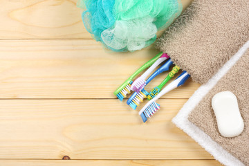 toothbrush tooth-brush with soap, bath towel and wisp of bast on wood background top view with copy space