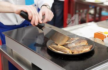 Chef frying seabass fillet