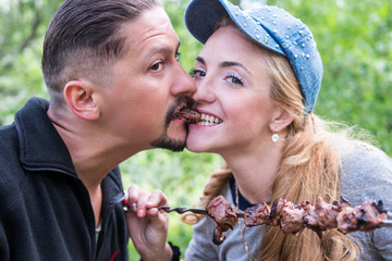 Man and woman eating shish kebab biting one piece of meat from both sides simultaneously