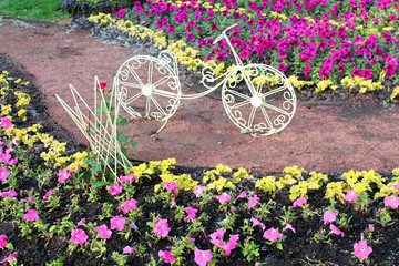 Decorative bicycle on a flower bed