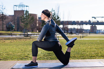 Young woman stretching her quadriceps muscles by grabbing her ankle during outdoor warming up routine in the park in a sunny day