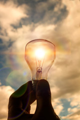 A light bulb above the sky and the sun at sunset. A lamp is a transparent lamp in an alternative human solar energy in urban, urban nightlife. Symbol, concept of business is a new creative idea.