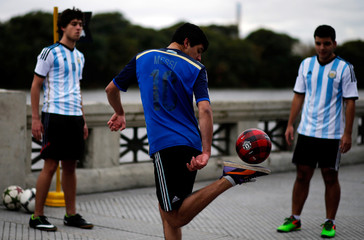 A boy wearing a Messi jersey plays with a ball before the unveiling of a statue of Argentina's soccer player Lionel Messi in Buenos Aires