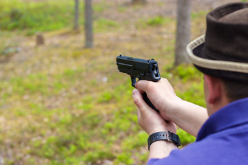 The man shoots from a pistol in the forest