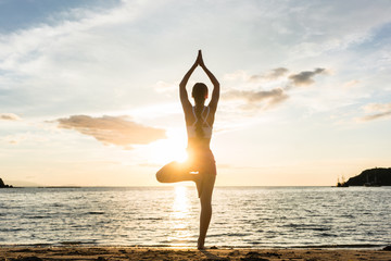 Foto op Plexiglas School de yoga Full length rear view of the silhouette of a woman standing on one leg while practicing the tree yoga pose on a tranquil beach, shot at sunset during summer vacation in Indonesia