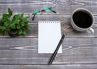 Blank notepad and pen with cup of coffee on office wood table background. Business concept with copy space for any desing