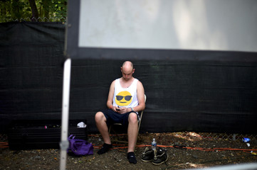 A man wearing a smiley face sleeveless shirt uses his phone during the Firefly Music Festival in Dover, Delaware, U.S.