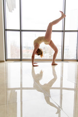 Beautiful girl ballerina dances near a window.