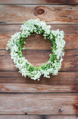 Wreath with white flowers on a wooden background. Rustic style
