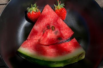 une figure réalisée avec un des morceaux de fruits , pastèque, fraise, kiwi dans un assiette noire