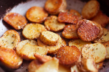Golden fried potatoes with seasonings on a frying pan