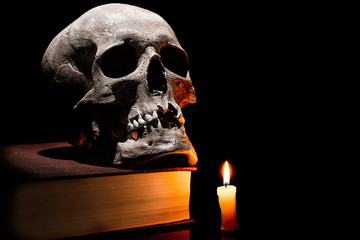 Human skull on old book with burning candle on black background