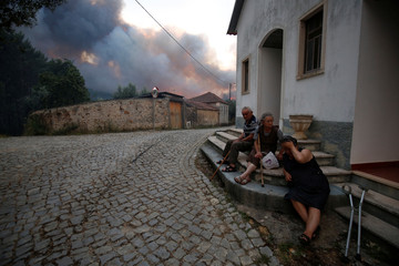 Villagers sit outdoors as a forest fire burns near the village of Fato central Portugal