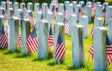 rows of gravestones with American flags in military cemetery