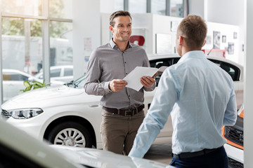 Outgoing client speaking with agent in automobile showroom