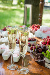 Festive table setting wineglasses with champagne, fruit and marshmallows. Wedding decor.