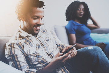 Smiling african american couple relaxing together on the sofa.Young black man using smartphones while rest at home in the living room. Horizontal,blurred background.Flares effect.