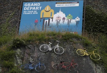 Painted bicycles are seen under a billboard announcing the second stage departure city of the 103rd Tour de France cycling event, in Saint-Lo