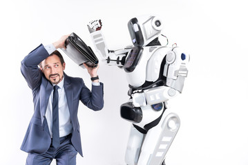 Adult frightened businessman is escaping from attacking robot