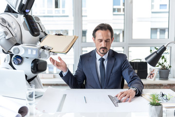 Adult businessman in suit is laboring with concentration