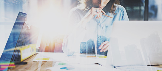 Young businesswoman working process at modern office.Account manager working at the wooden table with paper documents.Double exposure,skyscraper building blurred background.Wide,flares effect.