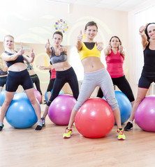 Sport and Fitness Concepts and Ideas. Group of Five Caucasian Female Athletes Having Exercises With Fitballs in Gym and Showing Thumbs Up Sign.