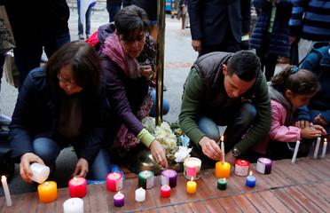 People light candles in the Andino shopping center after an explosive  device detonated in a restroom on Saturday, in Bogota