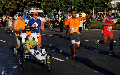 Rodrigo Rocha and his son Gabriel take part in the Rio Marathon in Rio de Janeiro