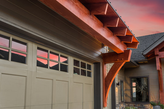 Beautiful Luxury Home Exterior Detail at Sunset: Garage Door with Partial View of Front Entrance and Colorful Sunset Sky