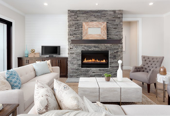 Beautiful living room interior with hardwood floors and fireplace in new luxury home. Couches at Right Angles are Opposite Armchairs and Fireplace with Surround Stretches from Floor to Ceiling