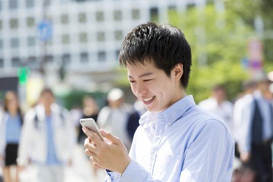 渋谷スクランブル交差点でスマホを見て笑みをこぼす男性