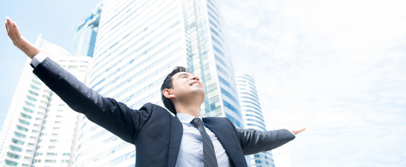 Businessman raising his arms, open palms, with face looking up to the sky